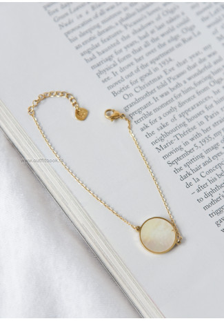 Gold tone bracelet with pearly white stone pendant