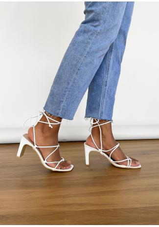 Sandalias blancas de tacón anudadas a la pierna